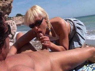 Une femme mure démontée sur la plage cris son plaisir