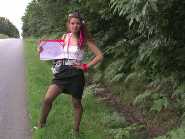 Une auto-stoppeuse en tenue sexy sur le bord de la route