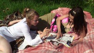 Deux jeunes femmes, une blonde et une brune, sont installées dans leur jardin pour...