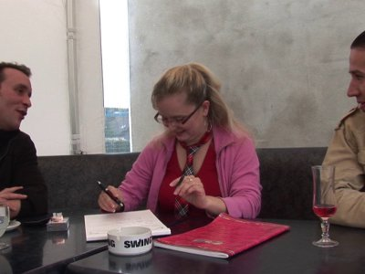 Une étudiante en pleine révision est assise sur la banquette d'un café. Une tabl